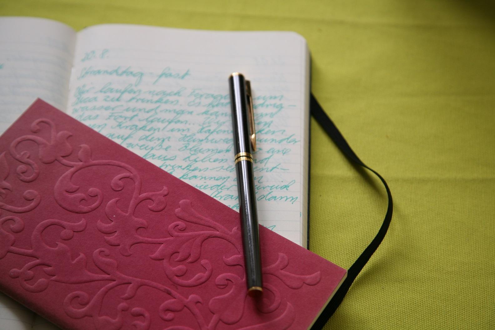 Notizbücher sind die Antwort auf die Frage Wohin mit den Buchstaben. Offenes Notizbuch mit grüner Schrift, Notizbuch mit geprägtem, rosafarbenem Einband und Füller mit Golddetails Denken und Schreiben