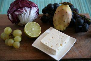 Radicchio, Trauben, Kaktusfeigen, Limette und Feta auf einem Holzbrett