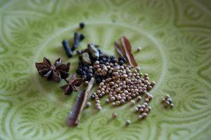 Sternanis, Koriander, Kardamom, Zimt, Pfeffer auf einem grünen Teller