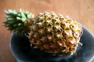 Ananasfrucht auf dunklem Teller